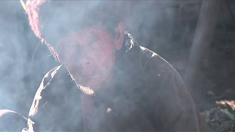 An-old-Chinese-man-looks-through-a-cloud-of-smoke