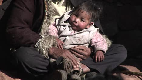 A-small-child-sits-in-a-poor-beggars-arms