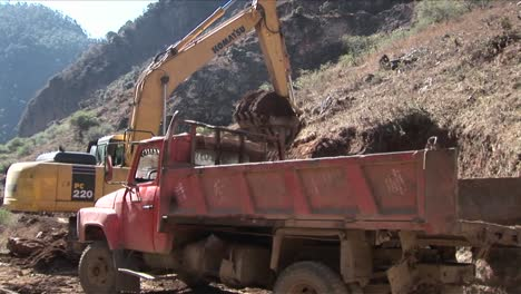 A-steam-shovel-moves-earth-into-a-dump-truck-along-a-rural-road