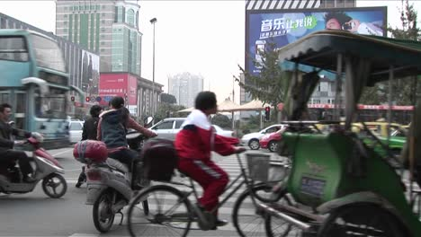 Large-amounts-of-traffic-pass-by-on-a-Beijing-China-street-with-modern-billboards-in-the-background