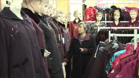 A-woman-shops-in-a-clothing-store-with-many-mannequins