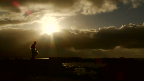 A-gorgeous-shot-as-a-fisherman-walks-in-front-of-the-sunset-with-his-net-in-slow-motion