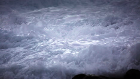 Water-level-view-of-waves-crashing-and-rolling-into-a-rocky-shore-in-slow-motion-1