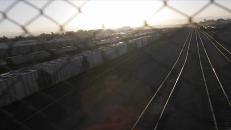 A-time-lapse-shot-through-a-chain-link-fence-of-a-railway-freight-yard