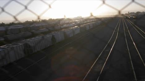 Un-Lapso-De-Tiempo-Filmado-A-Través-De-Una-Valla-De-Tela-Metálica-De-Un-Patio-De-Mercancías-Por-Ferrocarril