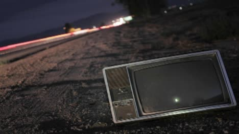 An-abandoned-TV-set-sits-along-a-highway-while-traffic-passes-in-time-lapse