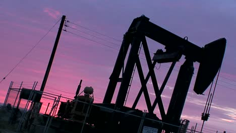 An-oil-derrick-pumps-against-a-purple-sky