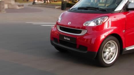 A-man-driving-a-red-Smart-car-through-a-city