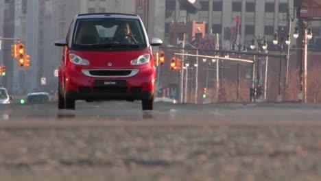 A-man-conduciendo-a-red-Smart-car-through-a-city-1
