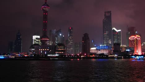 Boats-travel-across-a-cities-water-front-area-at-night