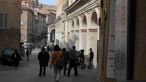 Una-Mujer-Con-Chaqueta-Roja-Sosteniendo-Una-Bolsa-Saliendo-De-Un-Antiguo-Edificio-De-Arquitecto