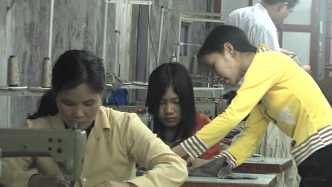 Eine-Asiatische-Frau-Unterrichtet-Eine-Näherin-Die-An-Einer-Nähmaschine-Sitzt