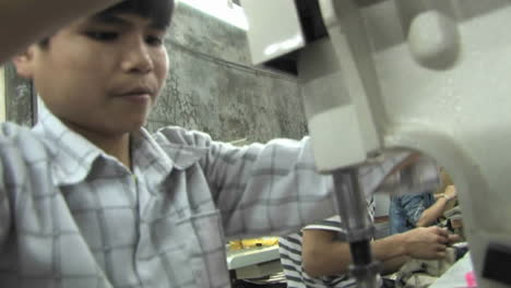 A-child-trying-to-fix-a-sewing-machine-with-the-help-of-a-wench-in-a-sweatshop-in-China