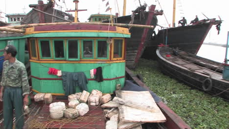 Fishing-boats-are-moored-at-a-dock-and-fishermen-prepare-nets