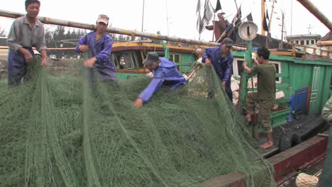 Men-gather-fishing-nets-from-a-boat