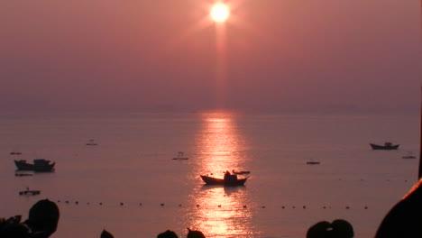 A-small-boat-at-sea-at-sunset-in-an-Asian-marina