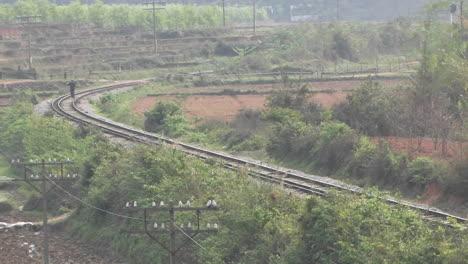 A-man-walks-between-railroad-tracks-at-a-bend