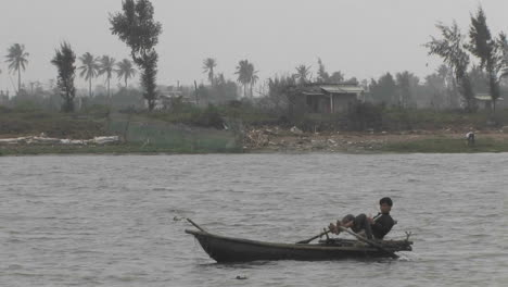 A-young-boy-is-sailing-a-boat-in-a-river-rowing-with-his-feet-on-the-Mekong-River-in-Vietnam