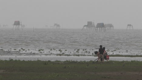 Two-children-and-one-adult-digging-in-sand-at-a-foggy-beach-in-Vietnam