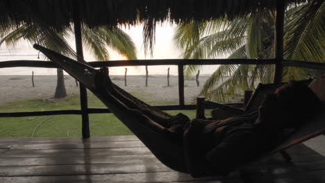 Time-lapse-of-man-sitting-in-a-hammock-in-palapa-at-La-Saladita-Beach-Guerrero-Mexico