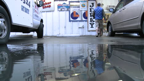 Man-jumping-over-water-puddle-at-a-store-in-Ojai-California