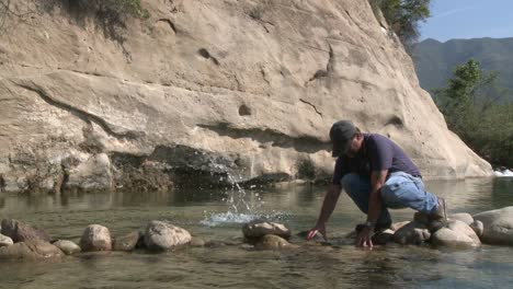Man-removing-rocks-from-a-fish-barrier-on-the-Ventura-River-Preserve-in-Ojai-California