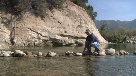 Man-removing-rocks-from-a-fish-barrier-on-the-Ventura-Río-Preserve-in-Ojai-California-1