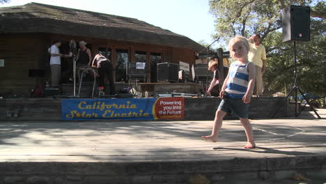 A-small-girl-dancing-along-on-a-stage-between-sets-in-Ojai-California