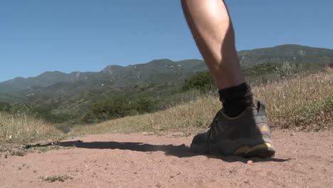 Low-angle-of-man-trail-running-on-the-Ventura-River-Preserve-in-Ojai-California