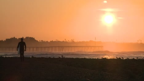 Surfer-silhouette-getting-out-of-the-water-during-sunrise-at-Surfers-Point-in-Ventura-California