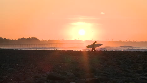 Wide-surfer-silhouette-getting-into-the-water-during-sunrise-at-Surfers-Point-in-Ventura-California