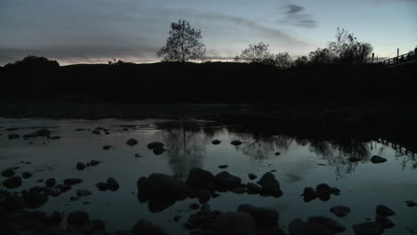 Wide-pan-at-dusk-of-light-reflecting-off-the-Ventura-River-and-the-sound-of-frogs-in-Oak-View-California