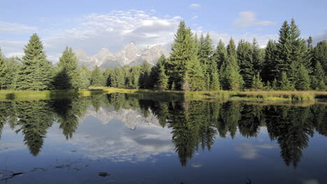 Slow-time-lapse-of-clouds-mountains-and-forest-reflecting-at-Schwabacher-Landing-in-Grand-Teton-National-Park-Wyoming