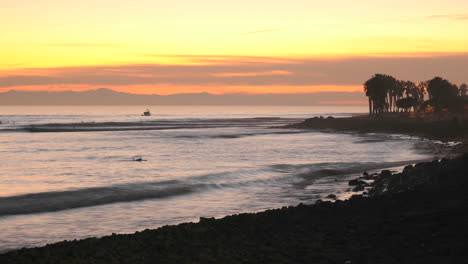 Time-lapse-of-waves-boat-and-surfers-at-Ventura-Point-after-sunset-in-Ventura-California