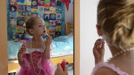 A-young-girl-applying-lip-gloss-while-playing-dress-up-in-the-mirror