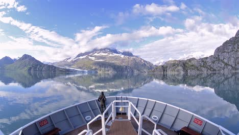 A-person-on-the-bow-of-a-ship-entering-Johns-Hopkins-Inlet-in-Glacier-Bay-National-Park-Alaska