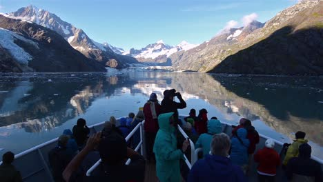 Tourists-on-the-bow-of-a-ship-entering-Johns-Hopkins-Inlet-in-Glacier-Bay-National-Park-Alaska