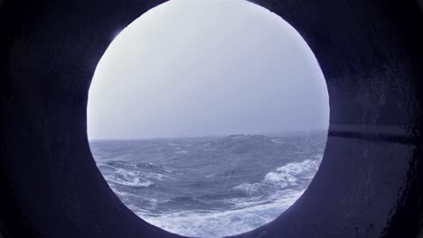 Porthole-view-of-big-waves-snow-and-high-winds-on-the-Drakes-Passage-heading-south-the-Antarctic-