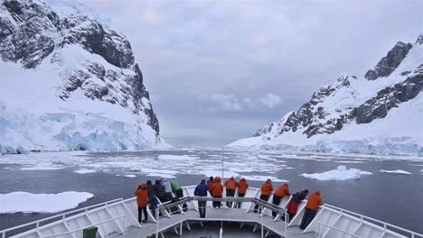 POV-of-ship-s-bow-with-tourists-in-the-ice-of-Lemaire-Channel-in-Antarctica-