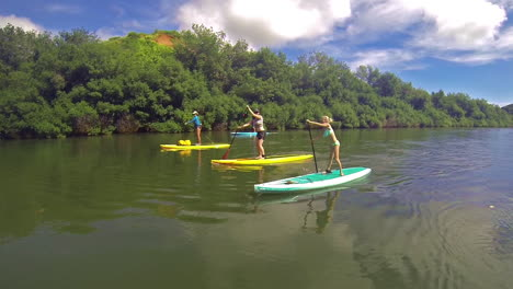 A-family-rows-paddleboards-down-a-river-in-Kauai-Hawaii