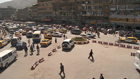 A-wide-establishing-shot-of-downtown-Kabul-Afghanistan-with-bus-taxi-and-vehicle-traffic