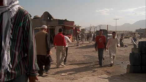 Slow-mo-shot-of-people-walking-on-dirt-streets-of-Kabul-Afghanistan