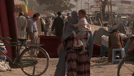Slow-mo-shot-of-a-woman-in-burka-walking-with-her-child-in-Kabul-Afghanistan