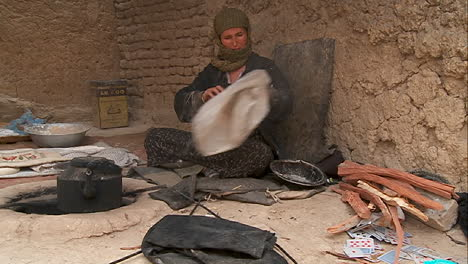 A-woman-puts-wood-into-a-tandor-oven-in-Kabul-Afghanistan