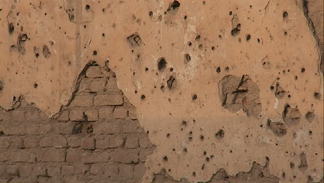 Tilt-up-of-bullet-holes-in-a-wall-in-Kabul-Afghanistan