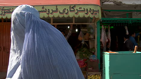 Woman-in-burqa-begging-in-front-of-shops-in-Kabul-Afghanistan