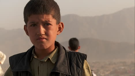 Close-up-portrait-of-boy-s-face-as-friends-fly-kites-in-an-empty-lot-in-Kabul-Afghanistan