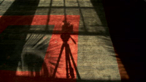 An-abstract-conceptual-shot-looking-at-the-shadow-made-by-a-film-camera-on-tripod-moving-in-shadow-in-time-lapse