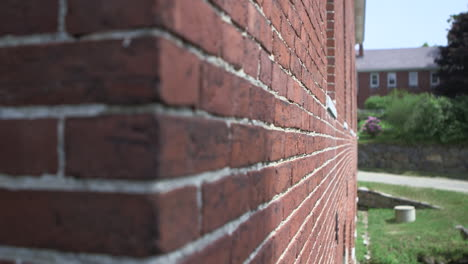 The-camera-moves-along-a-brick-wall-of-a-house-or-home