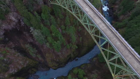 An-aerial-over-a-pickup-truck-traveling-over-a-steel-suspension-bridge-over-the-Skokomish-River-in-Washington-USA